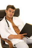 Doctor with open jacket with book sitting look. A Doctor with open jacket sitting and relaxing with a good book Royalty Free Stock Image