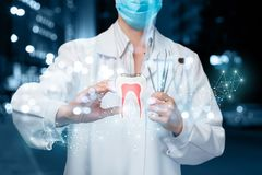 A doctor operating with the digital tooth model. A closeup of dentist operating with digital tooth model image and holding set of dental medicine tools at stock photo