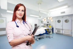 Doctor in operating theatre. A female doctor, general practitioner, surgeon, medical registrar or consultant with a background of a modern operating theatre with Royalty Free Stock Photography