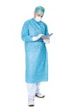 Doctor In Operation Gown Writing On Folder Royalty Free Stock Images