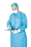 Doctor In Operation Gown Writing On Folder Royalty Free Stock Photo