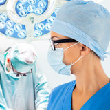 Doctor in operation room with surgeon on background royalty free stock photos
