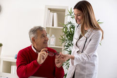 Doctor ophthalmologist giving glasses to patient after eyes exam Stock Photos