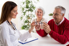 Doctor ophthalmologist giving glasses to patient after eyes exam Stock Photography