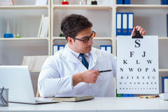 The doctor optician with letter chart conducting an eye test check Royalty Free Stock Photo