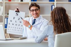 The doctor optician with letter chart conducting an eye test check Royalty Free Stock Image