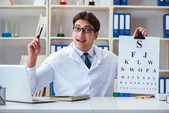 The doctor optician with letter chart conducting an eye test check Royalty Free Stock Photography