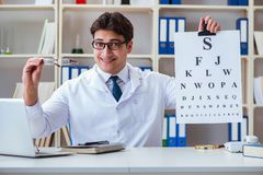 The doctor optician with letter chart conducting an eye test check Royalty Free Stock Photos