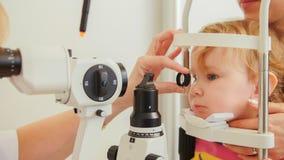 Doctor optometrist checks eyesight at little girl - child`s ophthalmology Stock Images