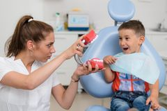 Doctor orthodontist playing with the boy in the dental office.  stock photo