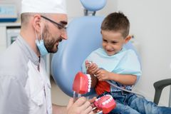 Doctor orthodontist playing with the boy in the dental office.  stock image