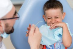 Doctor orthodontist playing with the boy in the dental office.  royalty free stock images
