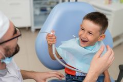 Doctor orthodontist playing with the boy in the dental office.  royalty free stock photography