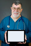 Doctor Holds a Computer Tablet with Blank Screen. A doctor or other medical professional holds a notebook computer displaying a blank screen Royalty Free Stock Images