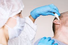 Doctor Otolaryngologist treats the otitis media patient. Buries the ear drops in the ear hole. On the face of a protective mask. stock images