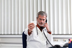 Doctor overstressed at his office desk Royalty Free Stock Photos
