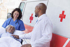 Doctor and paramedic wheeling in a elderly patient on a stretcher in front of an ambulance Royalty Free Stock Image