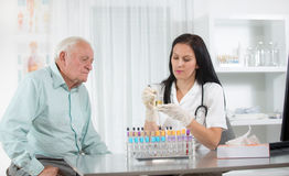 Doctor passes urine cups to patients Royalty Free Stock Photo