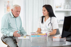 Doctor passes urine cups to patients Royalty Free Stock Photography
