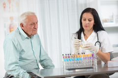 Doctor passes urine cups to patients stock image