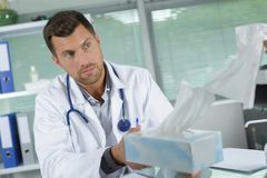 Doctor passing box tissues. Doctor passing box of tissues Stock Photography