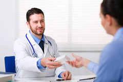 Doctor passing medicine to patient Stock Photos