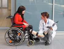 Doctor and patient. Female doctor consults with patient with leg in plaster Royalty Free Stock Image