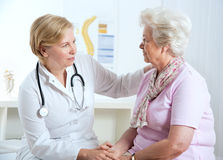 Doctor and patient. Doctor explaining diagnosis to his female patient Royalty Free Stock Photo