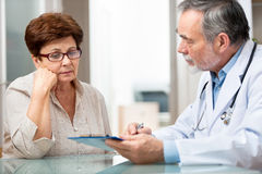 Doctor and patient. Doctor talking to his female patient at office Royalty Free Stock Photo