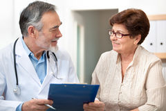 Doctor and patient. Doctor talking to his female patient at office Stock Photo