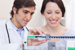 Doctor and patient adjusting the scale together Royalty Free Stock Images