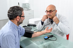 Doctor and Patient. With blood pressure meter in Doctor's office Royalty Free Stock Images