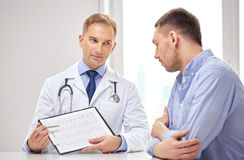 Doctor and patient with cardiogram on clipboard Royalty Free Stock Image