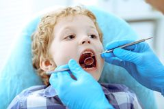 Doctor and patient child. Boy having his teeth examined with dentist. Medicine, health care and stomatology concept.  stock photo