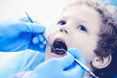 Doctor and patient child. Boy having his teeth examined with dentist. Medicine, health care and stomatology concept.  royalty free stock images