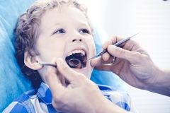 Doctor and patient child. Boy having his teeth examined with dentist. Medicine, health care and stomatology concept.  royalty free stock photos