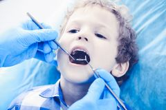 Doctor and patient child. Boy having his teeth examined with dentist. Medicine, health care and stomatology concept.  stock images