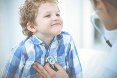 Doctor and patient child. Physician examining little boy. Regular medical visit in clinic. Medicine and health care stock photography