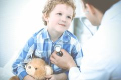 Doctor and patient child. Physician examining little boy. Regular medical visit in clinic. Medicine and health care stock photo