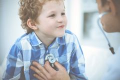 Doctor and patient child. Physician examining little boy. Regular medical visit in clinic. Medicine and health care royalty free stock photo