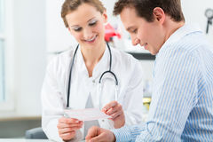Doctor with patient in clinic consulting. Female doctor with her patient in a consultation in clinic explaining something Royalty Free Stock Photo