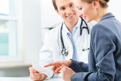 Doctor with patient in clinic consulting Stock Photo