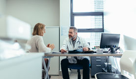 Doctor with patient during consultation in medical office. Medical specialist discussing with female patient in his clinic. Doctor with patient during royalty free stock image