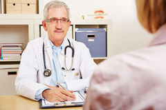 Doctor with patient during consultation. Old doctor talking with patient during a medical consultation Royalty Free Stock Image