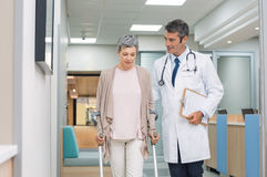 Doctor and patient with crutches. Mature doctor helping old female patient in crutches at the hospital. Physical therapist helping a women on crutches in a Royalty Free Stock Photos