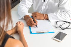 Doctor and patient are discussing about diagnosis. Medical doctor holding a stethoscope and taking notes. stock image