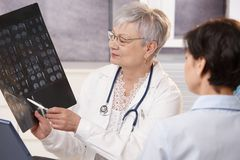 Doctor and patient discussing x-ray results. Royalty Free Stock Photography