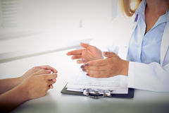 Doctor and patient are discussing something, just hands at the table Stock Image
