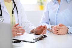 Doctor and patient are discussing something, just hands at the table Royalty Free Stock Photos