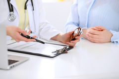 Doctor and patient are discussing something, just hands at the table Royalty Free Stock Photography